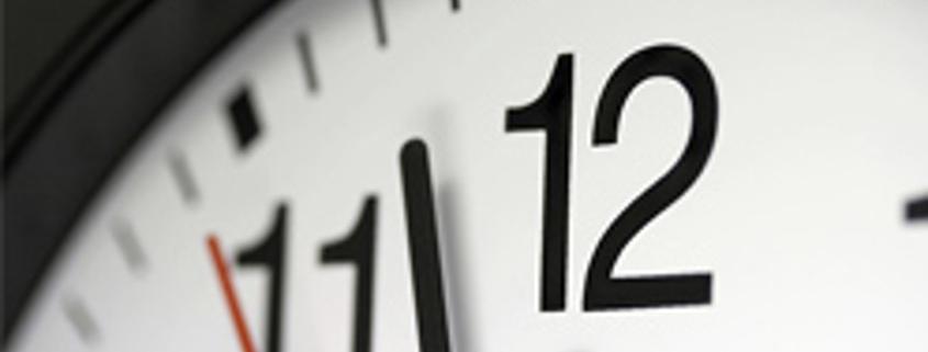 Clock dial showing hands approching 12 o' clock